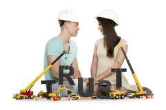 Het vestigen van vertrouwen: Het jonge paar met machines de bouw vertrouwen-wo-vertrouwt op Stock Fotografie