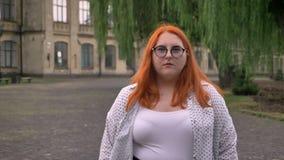 Het vette gembermeisje met glazen bevindt zich buiten in park in somber weer, lettend op bij camera stock footage