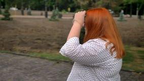 Het vette gembermeisje met glazen loopt in park in somber weer, het glimlachen, zijaanzicht stock videobeelden