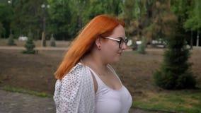 Het vette gembermeisje met glazen loopt in park in somber weer, zijaanzicht stock footage