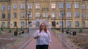 Het vette gembermeisje met glazen loopt in regenachtig weer, die paraplu houden, lettend op bij camera, glimlachen, die voortbouw stock videobeelden