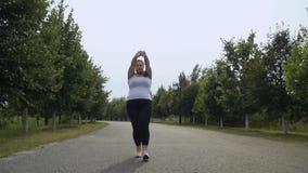 Het vette meisje loopt langs de weg stock videobeelden