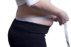 Het vette meisje meet de grootte van tailleconcept het verliezen van gewicht Horlogecijfer Het meten van band rond de taille stock afbeelding