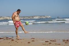 Het vette mens spelen met een bal op het strand royalty-vrije stock afbeelding