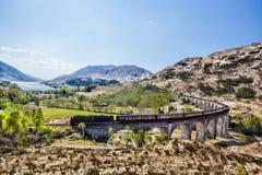 Het Viaduct van de Glenfinnanspoorweg in Schotland met de Jacobite-stoomtrein tegen zonsondergang over meer Royalty-vrije Stock Afbeeldingen