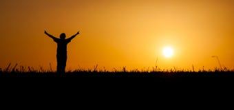 Het vieren van de persoon het leven bij zonsondergang stock afbeeldingen