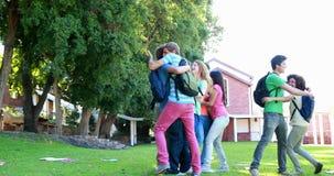 Het vieren van en studenten die boekt weg samen lopen werpen stock footage