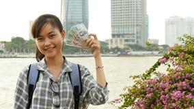 Het Vietnamese meisje houdt in haar handen en schept vijf honderdduizendenbenamingen van Vietnamees dong op royalty-vrije stock fotografie