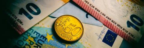 Het vijftig eurocentmuntstuk ligt op euro bankbiljetten royalty-vrije stock afbeeldingen