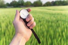 Het vinden van een richting in aard op een tarwegebied Een mensen` s hand houdt een kompas stock foto