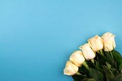 Het vlakke boeket van beige rozen op blauwe achtergrond, legt, hoogste mening, exemplaarruimte De dag van moeders Rood nam toe Royalty-vrije Stock Fotografie