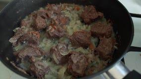 Het vlees is gebraden in een pan met uien en wortelen Het kokende Thaise traditionele voedsel van Azië Saus van de bellen de olie stock footage