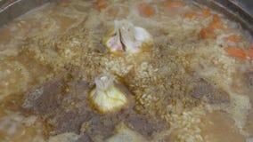Het vlees met rijst, knoflook en groenten is dicht omhoog gekookt in een ketel bij de staak Voorbereiding van pilau stock video