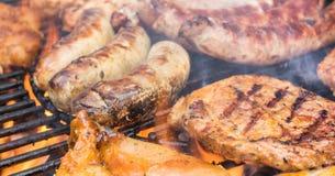 Het vlees op de grill roostert in de brand stock afbeelding