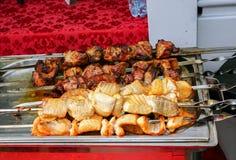 Het vlees op de grill wordt gekookt is op een metaaldienblad dat stock afbeeldingen
