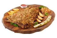 Het vlees roosterde ribben op een witte achtergrond, op een raad met aardappelen in de schil, komkommers en legde paddestoelen in Royalty-vrije Stock Afbeelding