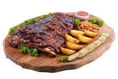 Het vlees roosterde ribben op een witte achtergrond, op een raad met aardappelen in de schil, komkommers en legde paddestoelen in Royalty-vrije Stock Afbeeldingen