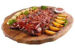 Het vlees roosterde ribben op een witte achtergrond, op een raad met aardappelen in de schil, komkommers en legde paddestoelen in Stock Afbeelding