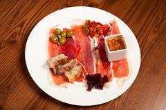 Het vlees van de delicatessenwinkel op een witte plaat Royalty-vrije Stock Fotografie