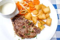 Het vlees van het lapje vleesrundvlees met tomaat en frieten Royalty-vrije Stock Foto's