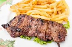 Het vlees van het lapje vleesrundvlees met tomaat en frieten royalty-vrije stock foto