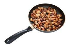 Het vlees van het varkensvlees dat op de pan wordt gebraden die over wit wordt geïsoleerdr Stock Foto's