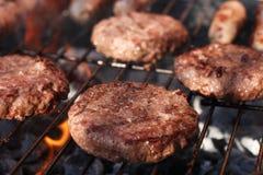 Het vlees van het voedsel - burgers bij de barbecuegrill. Stock Fotografie