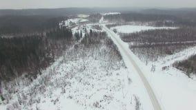Het vliegen boven landelijke weg door bos in slechte de winter bewolkte dag met sneeuwval stock footage