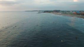 Het vliegen boven Surfers die in Oceaan op de Grote Golf in de Avond wachten stock video