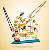Het vliegen de sushistukken dienden op houten die plaat, op gekleurde achtergrond wordt gescheiden stock afbeelding
