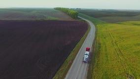 Het vliegen hoog boven vracht semi vrachtwagen die goederen op bezige weg over het land in mooie de zomeravond vervoeren stock videobeelden