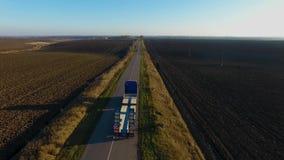 Het vliegen hoog boven vracht semi vrachtwagen die goederen op bezige weg over het land in mooie de zomeravond vervoeren stock footage