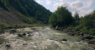 Het vliegen laag boven de rivier die zijn manier snijden door de de lentevallei 4K stock footage