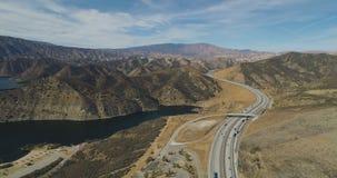 Het vliegen langs een weg van de woestijnberg naast een reservoir stock videobeelden