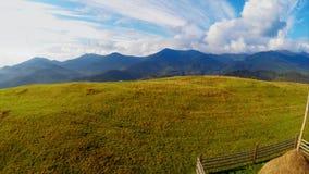 Het vliegen over berglandschap met hooistapel bij weide stock video