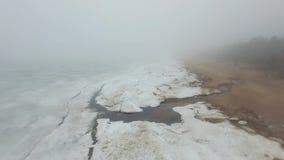 Het vliegen over bevroren overzeese kustlijn in nevelige koude de winterdag stock footage