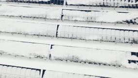 Het vliegen over de landbouwbedrijfzonnepanelen in de winter na de cycloon Comités onder de sneeuw stock footage