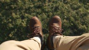 Het vliegen over de mooie bosbomen Lucht geschotene camera en menselijke benen met blauwe tennisschoenen in kader Landschap stock video