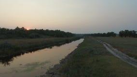 Het vliegen over de rivier bij zonsondergang stock video