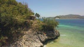 Het vliegen over het groene eiland in oceaan met dorp en zandstrand stock footage