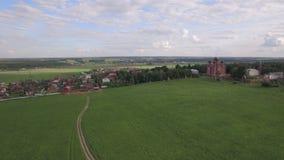 Het vliegen over groene weiden en Lukino-Dorp in Rusland stock video