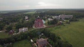 Het vliegen over Lukino-Dorp met Kathedraal van Beklimming stock video