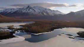 Het vliegen over meren met ijs met snowcapped rond bergen stock footage