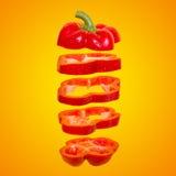 Het vliegen rood capsicum Gesneden drijvende groene paprika op een oranje achtergrond Levity groente Stock Afbeelding