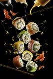 Het vliegen stukken sushi met houten die eetstokjes en saus, op zwarte achtergrond worden geïsoleerd Vliegend voedsel en motiecon stock foto's