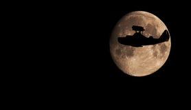 Het vliegende silhouet van het bootvliegtuig op de gehele achtergrond van de Maanoppervlakte Stock Afbeelding