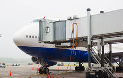 Het vliegtuig bij de passagiers van de luchthavenlading stock afbeeldingen