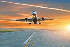 Het vliegtuig gaat van de baan in de avond van start bij de luchthaven royalty-vrije stock afbeelding