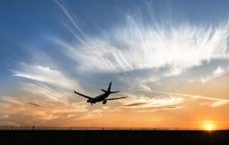 Het vliegtuig landt bij de zonsondergang Stock Fotografie