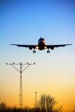Het vliegtuig landt bij zonsondergang Stock Foto